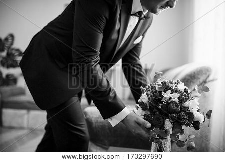 Groom With Wedding Bouquet At His Room At Morning Day. Black And White Photo