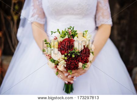 Close Up Wedding Bouquet With Red And White Flowers At Hands Of Bride.