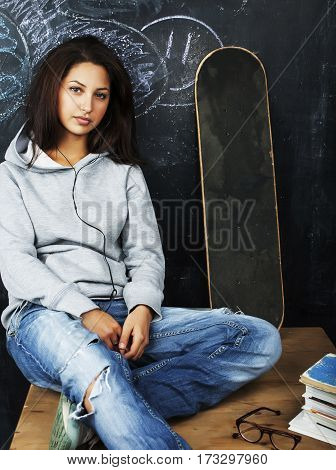 young cute teenage girl in classroom at blackboard seating on table smiling, problem hooligan close up, lifestyle people concept