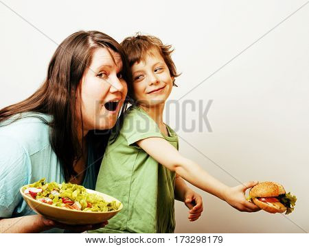 fat woman holding salad and little cute boy with hamburger on white background, teasing