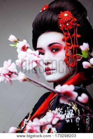 young pretty geisha in black kimono among sakura, asian ethno close up among sakura