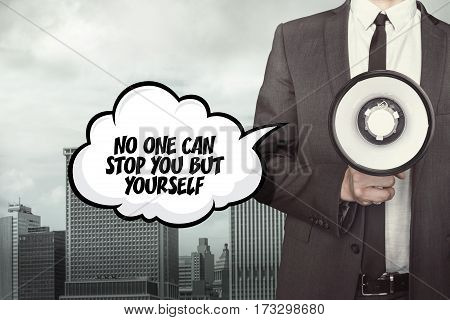 No one can stop you but yourself text on speech bubble with businessman holding megaphone