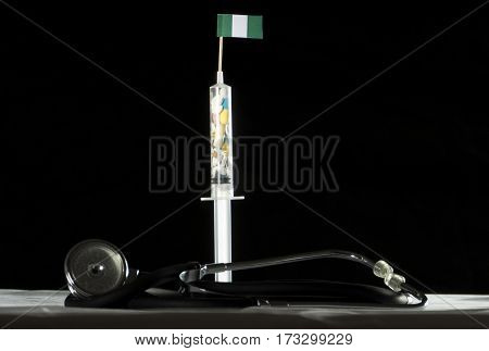Stethoscope And Syringe Filled With Drugs Injecting The Nigerian Flag On A Black Background