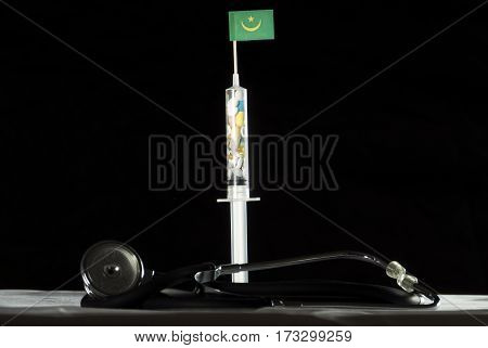 Stethoscope And Syringe Filled With Drugs Injecting The Mauritanian Flag On A Black Background