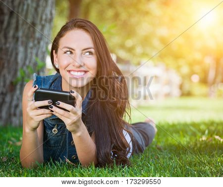 Attractive Happy Mixed Race Young Female Laying In The Grass Texting on Her Cell Phone Outside.