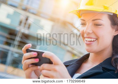 Young Professional Female Contractor Wearing Hard Hat at Construction Site Texting with Cell Phone.