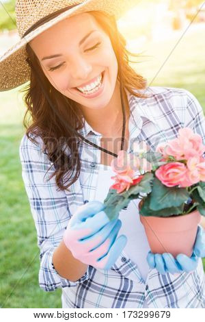 Happy Young Adult Woman Wearing Hat and Gloves Gardening Outdoors.