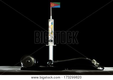 Stethoscope And Syringe Filled With Drugs Injecting The Eritrean Flag On A Black Background