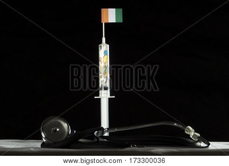Stethoscope And Syringe Filled With Drugs Injecting The Ivory Coast Flag On A Black Background