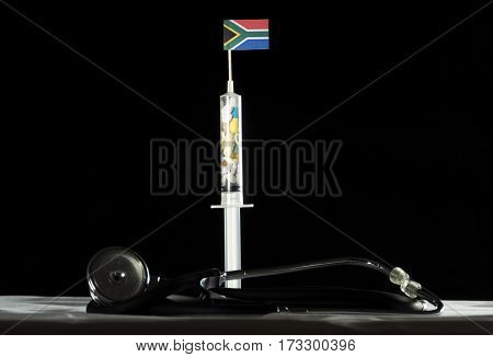 Stethoscope And Syringe Filled With Drugs Injecting The South African Flag On A Black Background
