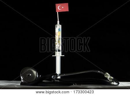 Stethoscope And Syringe Filled With Drugs Injecting The Turkish Flag On A Black Background