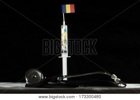 Stethoscope And Syringe Filled With Drugs Injecting The Chadian Flag On A Black Background