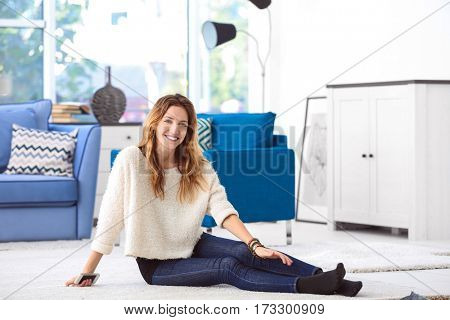 Portrait of young woman sitting on floor in room