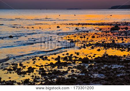 Stones In Water, Waves On Sandy Beach Of Gulf Of Finland And Wonderful Sunset