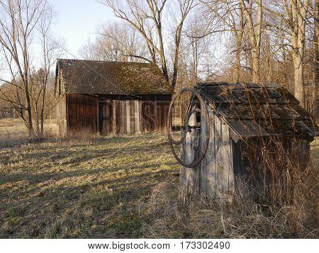 stara drewniana studnia i stodoła wśród drzew