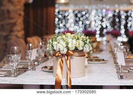 hat box with flowers close-up. Wedding. Banquet. The chairs and table for guests, served with cutlery and crockery