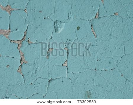 The texture of a wall with cracked blue paint
