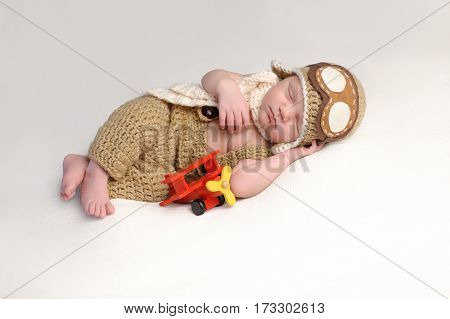 Sleeping two week old newborn baby boy wearing an aviator hat and outfit.