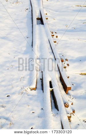 closeup of snow covered rusty rails junction