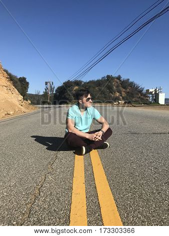 Young adult tourist man sitting on asphalt road during the trip at hot summer day