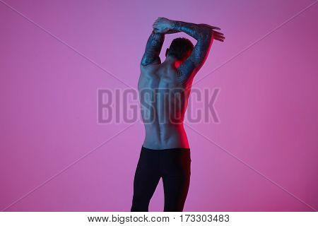 Studio fashion portrait of sexy sporty man. Muscular naked torso from back on a pink background.