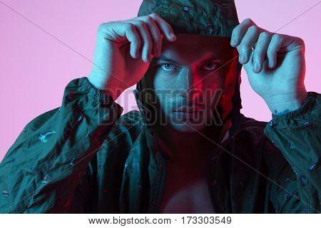 Portrait of sport fit attractive man in sportswear hoodie color studio flash light