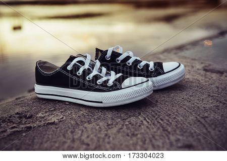 Vintage black and white shoes on the asphalt road