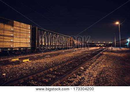 Industrial cargo train on railroad track at night time