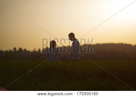 couple walking through the field and holding hands over sunset