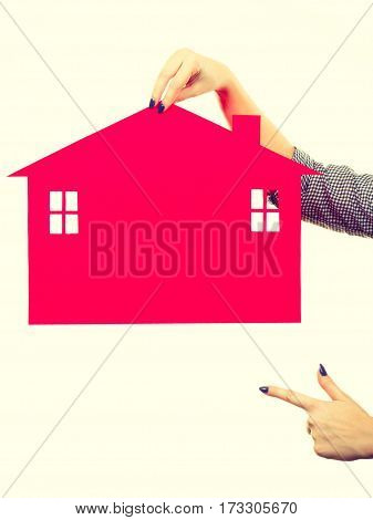 Ownership and property concept. Woman hand holding red paper house moving to new home.