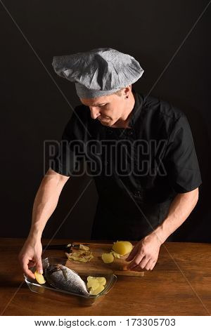 chef preparing a fish dish with garnish
