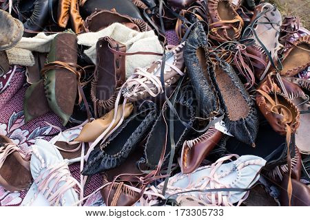 Pile of traditional Romanian leather peasant sandals.