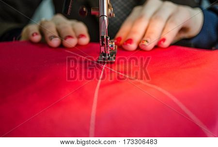 A Seamstress, Red Fabric, Women's Hands, Hands Guiding The Cloth In A Sewing Machine
