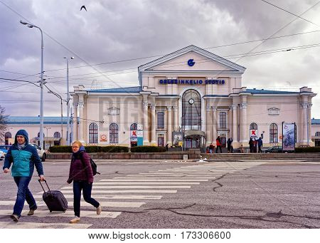 Vilnius Lithuania - February 25 2017: Travelers with luggage at pedestrian crossing near Train Station in Vilnius Lithuania