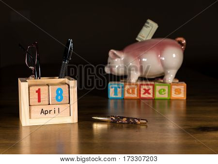 Wooden letters in calendar showing tax day for filing is April 18 2017 with savings piggy bank in background