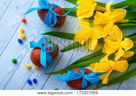 Easter eggs and fresh spring daffodils on weathered wooden background