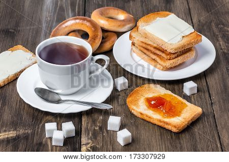 Tasty and healthy breakfast with cup of tea, bread, bagel, butter and homemade jam on wooden table, closeup, shallow depth of field