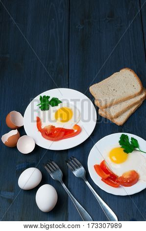 Top view tasty healthy breakfast: spiced with greens and pepper fried egg in small plate on old wooden rustic table and three slices of fresh bread, eggshell, eggs and fork.