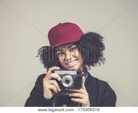 Portrait of pretty african smileing young teenage hipster woman model with retro photo camera wearing a pink hat, black leather jacket. Fashion look. Isolated on white background in studio.