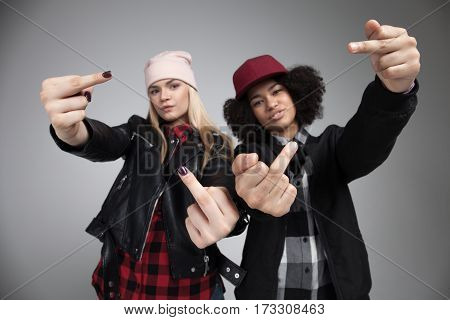 Studio lifestyle portrait of two best friends hipster girls wearing stylish bright outfits, going crazy and say fuck off. Isolated on white background.