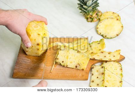 Male Hands Cutting  Pineapple On A Wooden Board