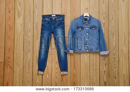 Jeans jacket with Blue jeans trousers ,hat- wooden background