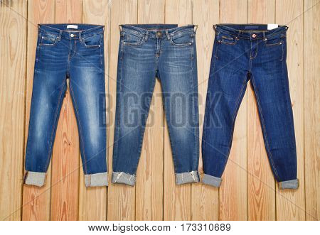 Three blue Jeans - wooden background