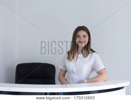 Beautiful female receptionist at dental or medical clinic smiling.