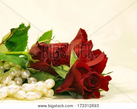 Bunch of red roses with pearl necklace