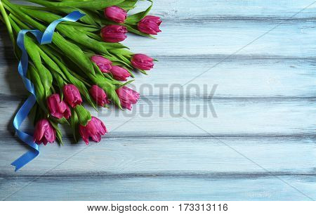 Purple beautiful tulips with ribbon on wooden background