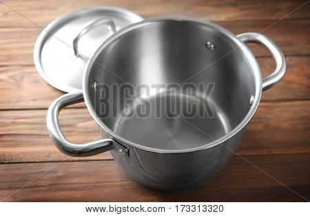 Stainless saucepan on wooden table