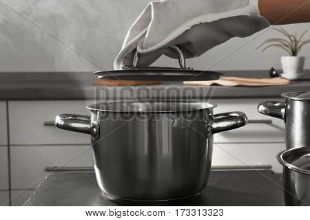 Woman hand in mitten holding lid above metal pan in kitchen