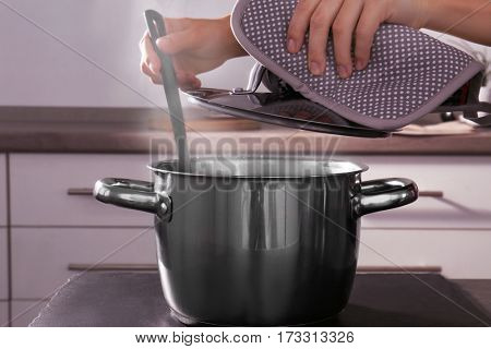 Woman hand mixing food in metal pan in kitchen