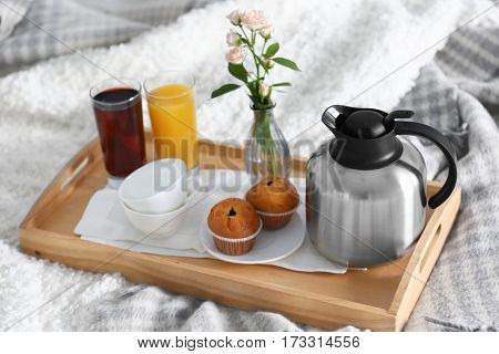 Breakfast in bed. Tray with juice, muffins and coffee